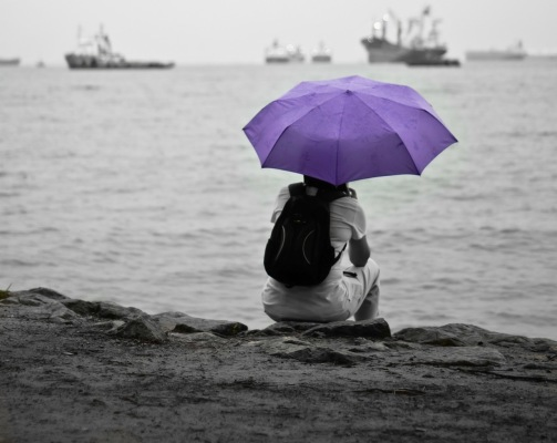 person sits on shore under umbrella